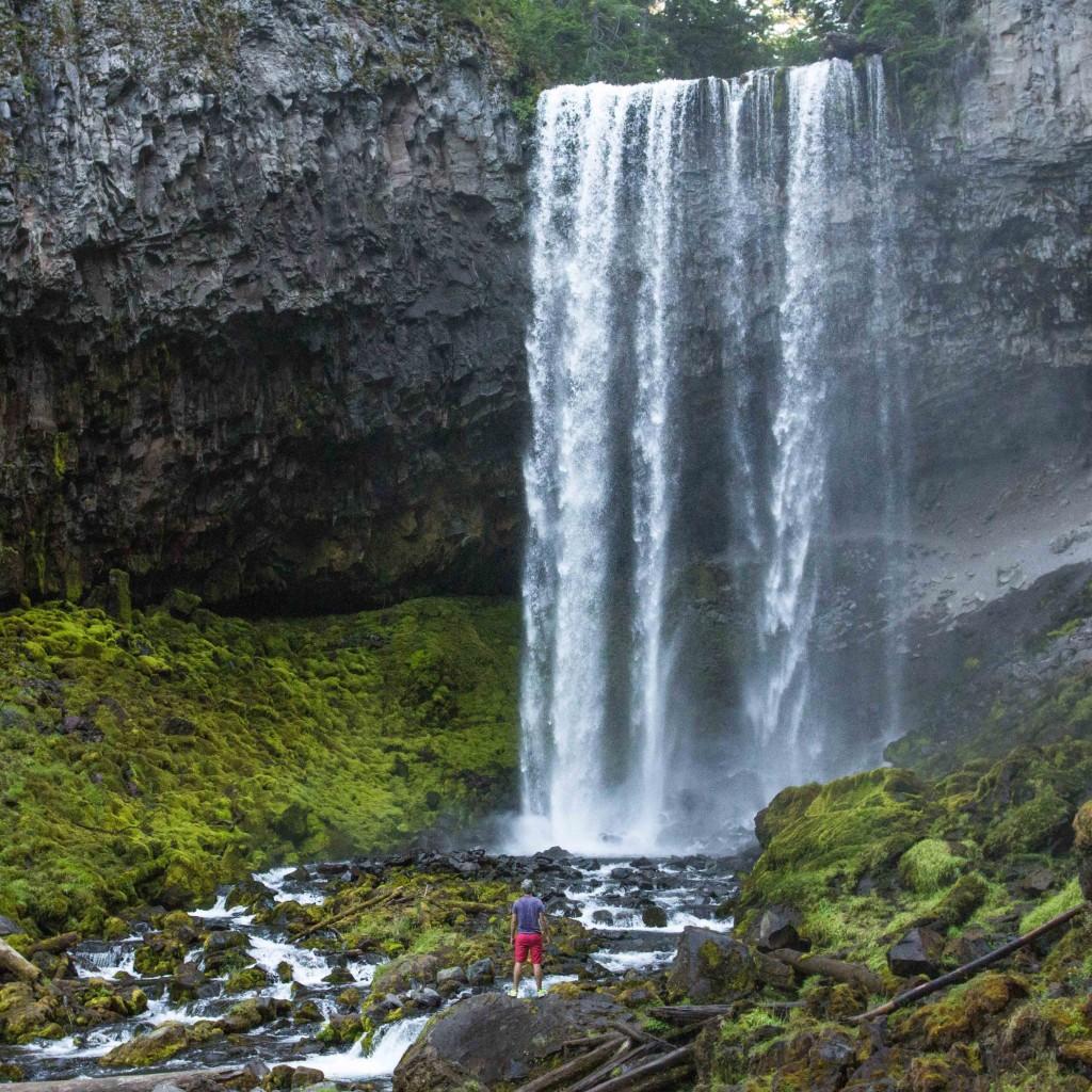 standing before waterfall